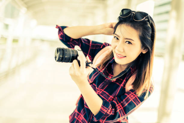 beautiful happiness young asian girl in casual dress traveling alone at train station or airport with backpack vintage tone photo concept stock photo