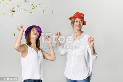 627933752istockphoto Beautiful happy and smiling girlfriends at the party. Dancing and celebrating time 1043605106