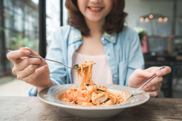 Schöne fröhliche asiatische Frau, die einen Teller mit italienischen Meeresfrüchten Spaghetti im Restaurant oder Café isst, während sie lächelt und sich das Essen anschaut. – Foto