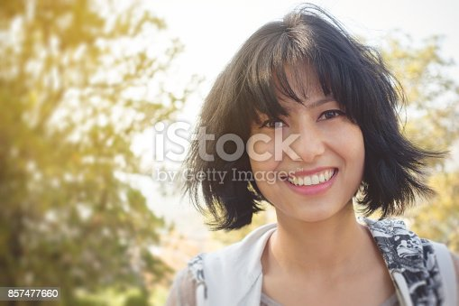 istock Beautiful happy Asian young woman looking at camera with smile. 857477660