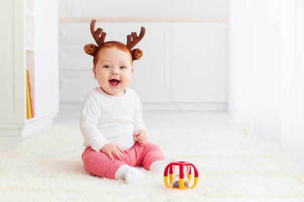 schönes glückliches baby hirsch spielen mit spielzeug zu hause - weihnachten 7 jährige stock-fotos und bilder