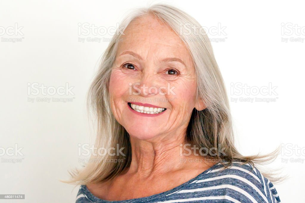 Beautiful happy blond mature woman smiling, white background, copy space stock photo