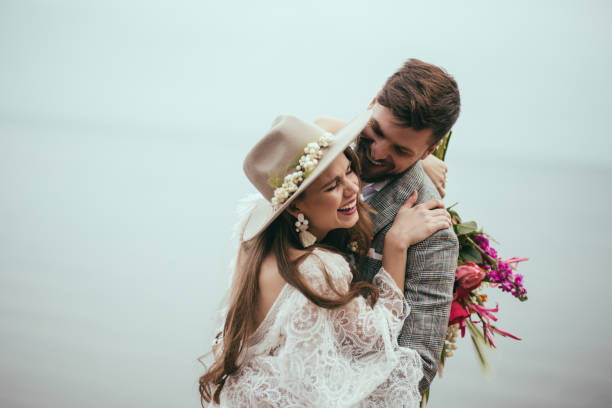 beautiful happy bride and groom in boho style laughing at lake stock photo