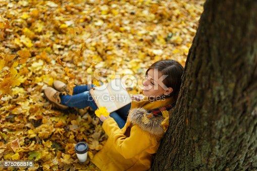 istock Una hermosa mujer de pelo castaño feliz en capa amarilla y los pantalones  vaqueros sentados 1ecf863f21de