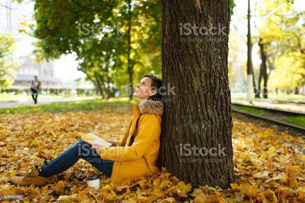 Hermosa mujer de pelo castaño feliz en capa amarilla y los pantalones  vaqueros sentados debajo del efadca0d32c8