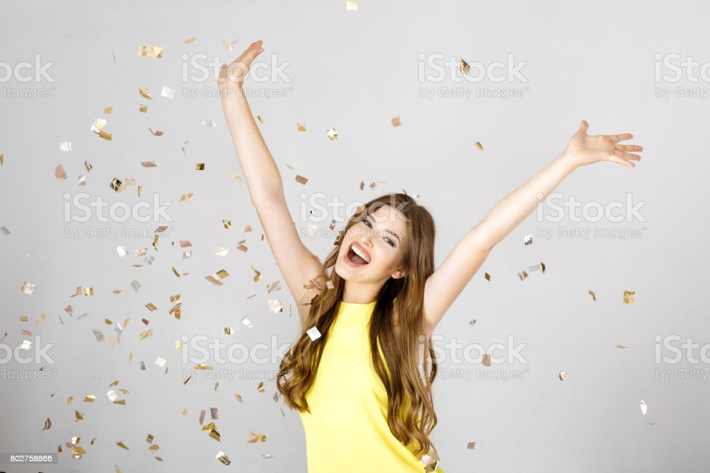 Beautiful happy brunette woman with long hair smiling and confetti falls everywhere. party time stock photo