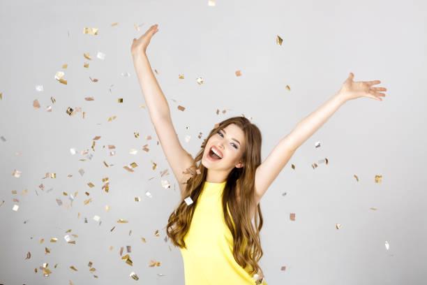 Belle femme brune heureuse avec cheveux longs souriant et confettis tombe partout. temps de partie - Photo
