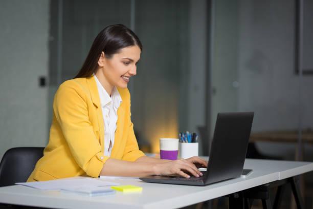 Beautiful happy businesswoman working on laptop stock photo