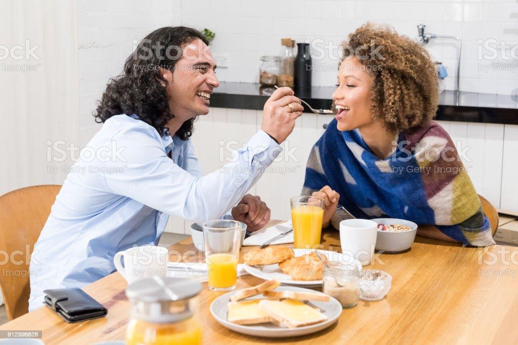Mooie gelukkige paar ontbijt eten in de keuken foto