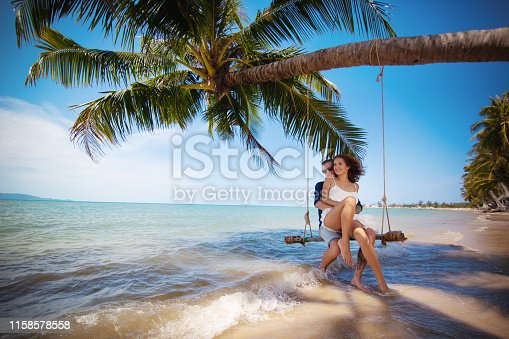Beautiful happy couple on swing tropical beach, honeymoon vacation concept