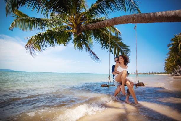 vackra lyckliga par på swing på tropisk strand, smek månad semester koncept - smekmånad bildbanksfoton och bilder