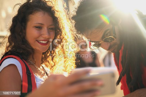 507375092istockphoto Beautiful happy curly girl is showing her boyfriend content on her phone that made him very curious. 1032717022