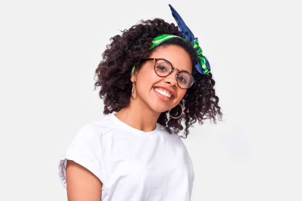 Beautiful happy dark-skinned young woman dressed in white t-shirt, enjoying the weather. African American female smiling broadly, wearing round eyewear posing over white studio wall stock photo