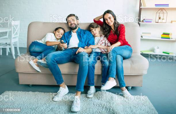 Beautiful happy family watch tv on the couch at home and smiling picture id1130953506?b=1&k=6&m=1130953506&s=612x612&h=3pvfzcgmlkufqiydmywyg4aoqhigwclfy3e6b6mqn2i=