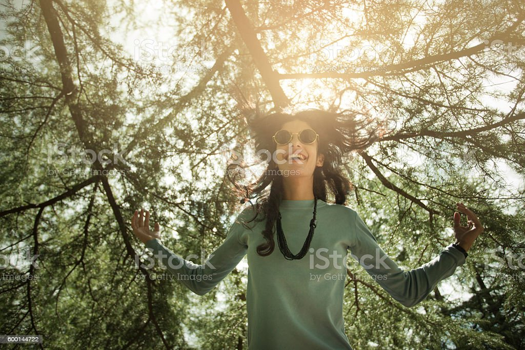 Beautiful, happy girl expressing freedom and jumping under pine trees. stock photo