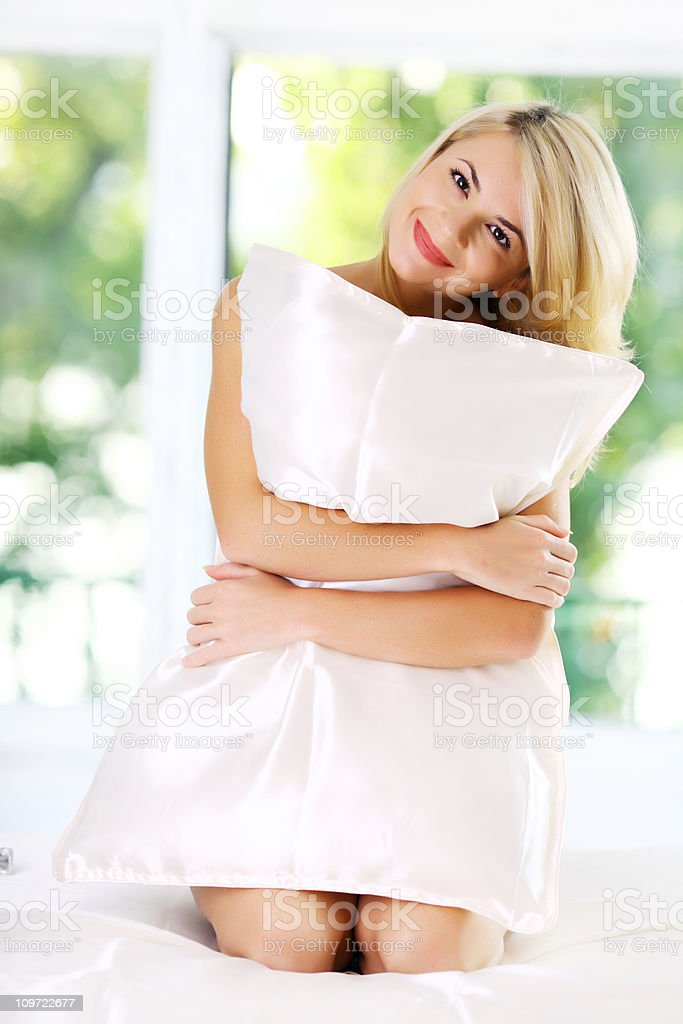 Beautiful happy girl holding pillow. royalty-free stock photo
