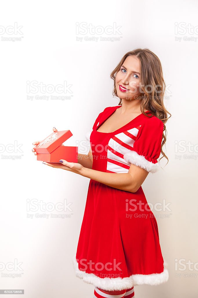Beautiful Happy girl in Santa Claus clothes opens a gift zbiór zdjęć royalty-free