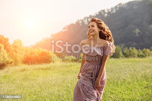 Beautiful happy girl walking by the field