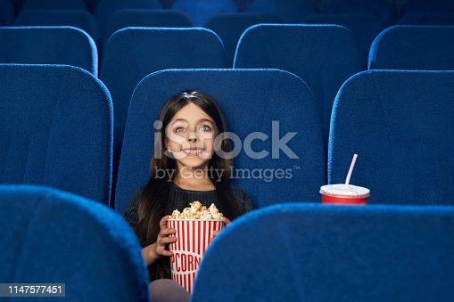 istock Beautiful, happy girl watching movie with popcorn in cinema. 1147577451