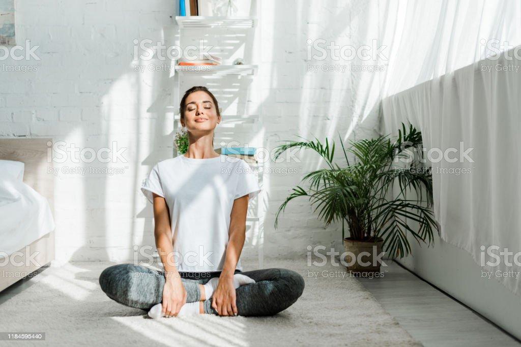 belle fille heureuse avec les yeux fermés pratiquant le yoga dans la position de lotus dans la chambre à coucher le matin - Photo de Adulte libre de droits