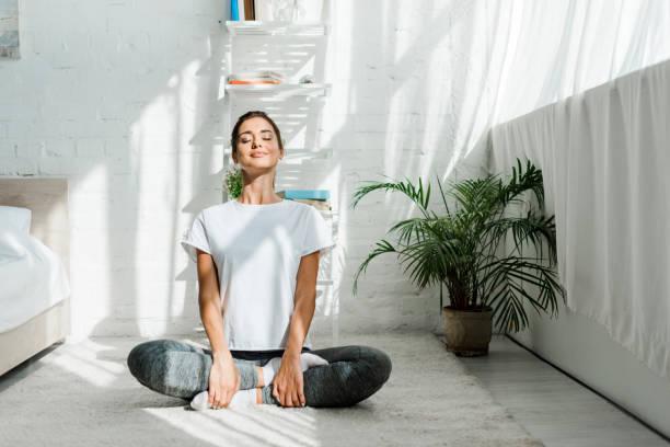 美麗的快樂女孩閉上眼睛練習瑜伽在蓮花位置在臥室在早上 - 幸福 個照片及圖片檔