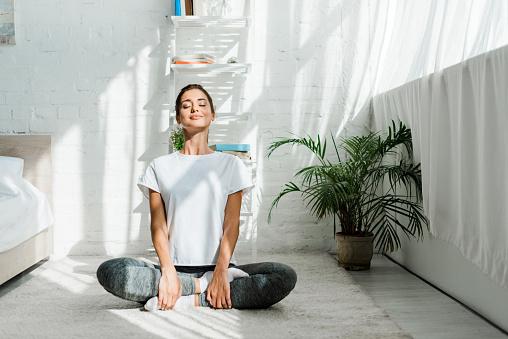 Hermosa Chica Feliz Con Los Ojos Cerrados Practicando Yoga En Posición De Loto En El Dormitorio En La Mañana Foto de stock y más banco de imágenes de Actividades y técnicas de relajación