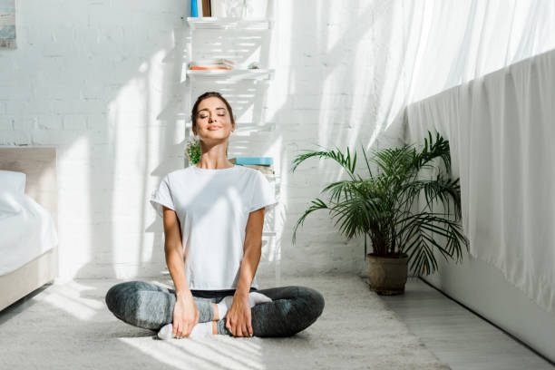 beautiful happy girl with closed eyes practicing yoga in lotus position in bedroom in the morning - casa imagens e fotografias de stock