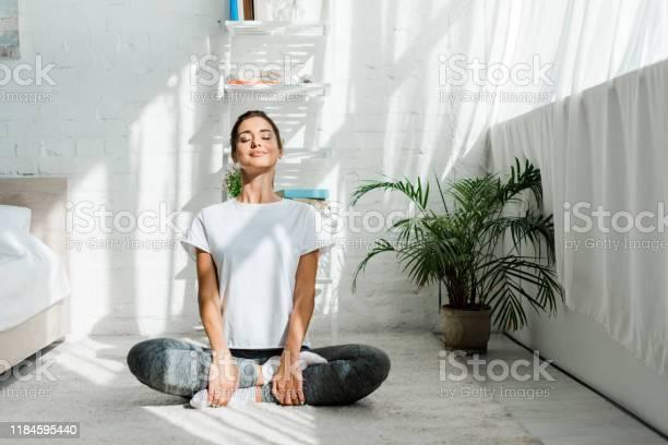 Photo libre de droit de Belle Fille Heureuse Avec Les Yeux Fermés Pratiquant Le Yoga Dans La Position De Lotus Dans La Chambre À Coucher Le Matin banque d'images et plus d'images libres de droit de Adulte