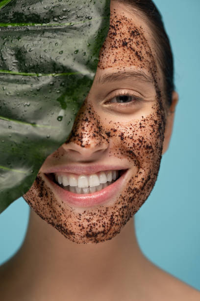 beautiful happy girl with coffee scrub on face, isolated on blue with leaf stock photo