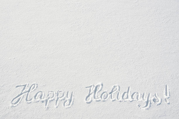 Beautiful Happy Holidays letters calligraphy handdrawn on flat snow surface stock photo