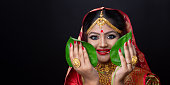 istock A beautiful happy Indian bride holding betel leaf 1175943985