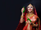 istock A beautiful happy Indian bride holding betel leaf 1175944100