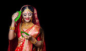 istock A beautiful happy Indian bride holding betel leaf 1175944109