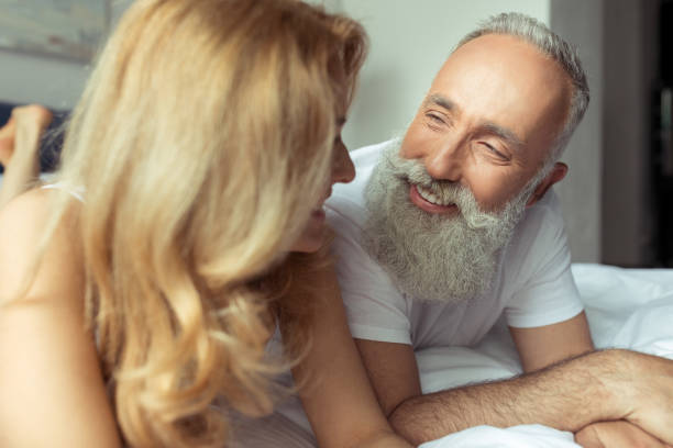 Beautiful happy mature couple lying together in bed and smiling each other stock photo