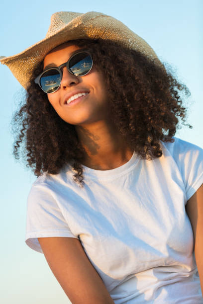 a4a2ab7c5516a leather cowboy hat stock photo. Beautiful happy mixed race African American  female girl teenager young woman wearing relective aviator sunglasses and