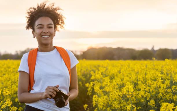 Hermosa raza mixta afroamericana adolescente mujer joven sonriendo al aire libre con dientes perfectos tomando fotografías con una cámara en un campo de flores amarillas - foto de stock