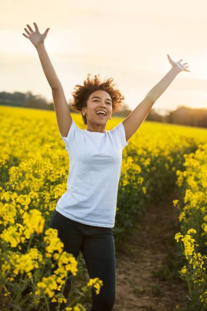 Hermosa raza mixta feliz afroamericana adolescente mujer joven sonriendo brazos riendo levantados celebrando en el campo de flores amarillas al atardecer - foto de stock