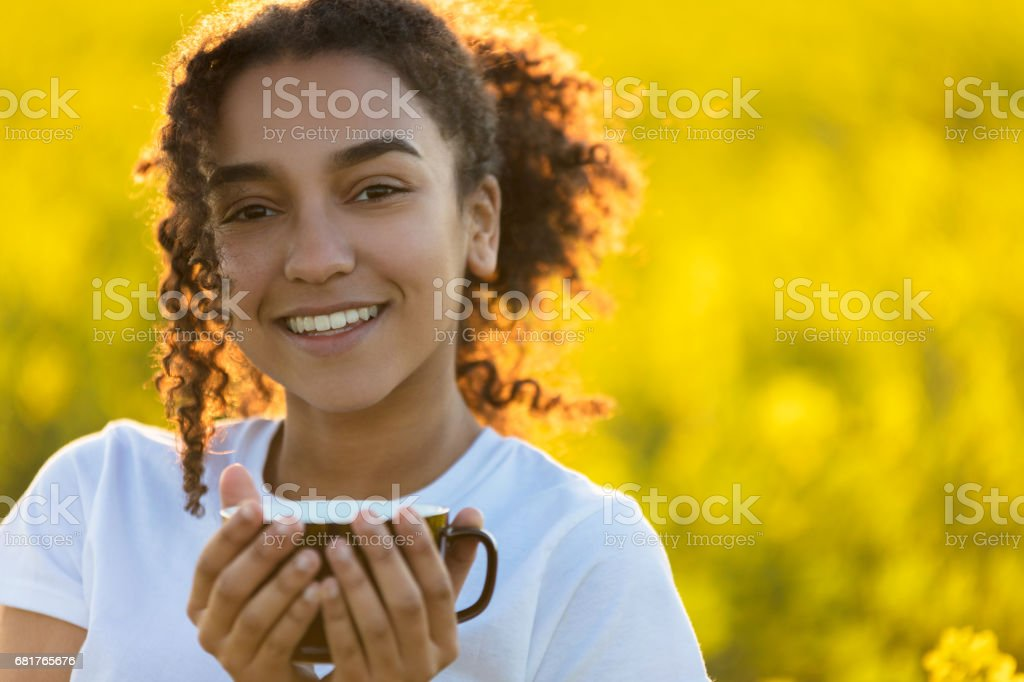 Beautiful happy mixed race African American girl teenager female young woman smiling drinking coffee or tea outdoors stock photo
