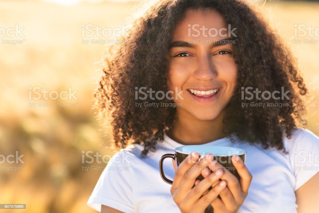 Beautiful happy mixed race African American girl teenager female young woman smiling with perfect teeth white,drinking coffee or tea outdoors stock photo