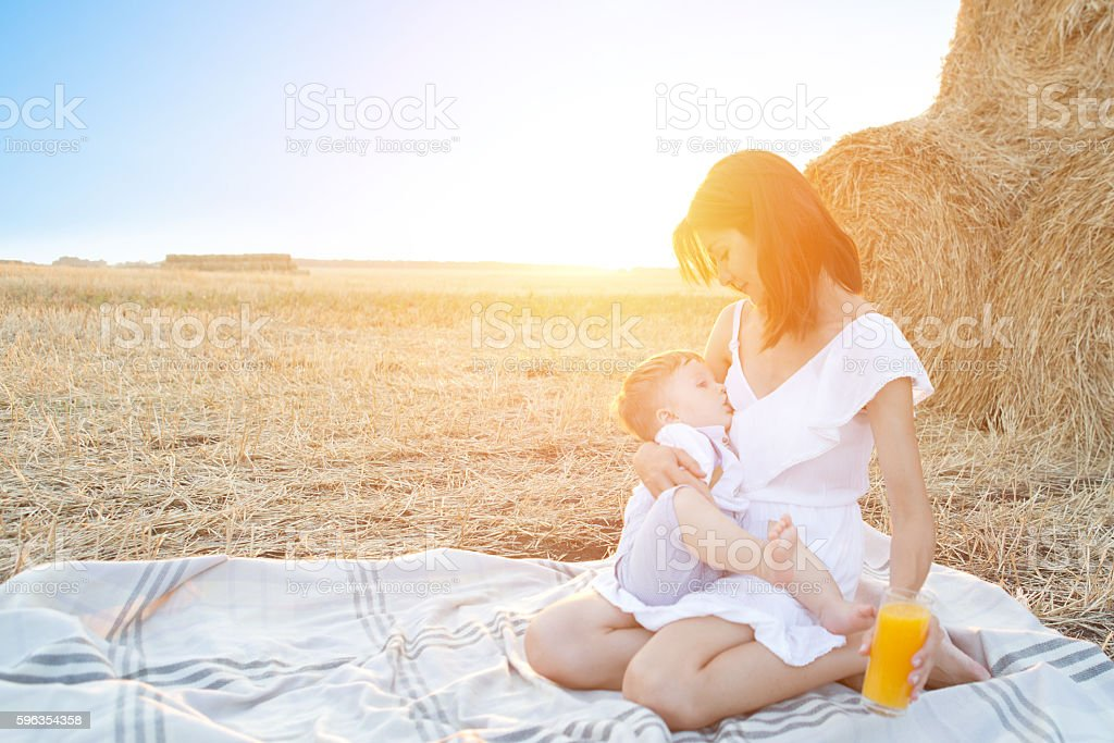 Beautiful happy mother breastfeeding her baby boy outdoor. royalty-free stock photo