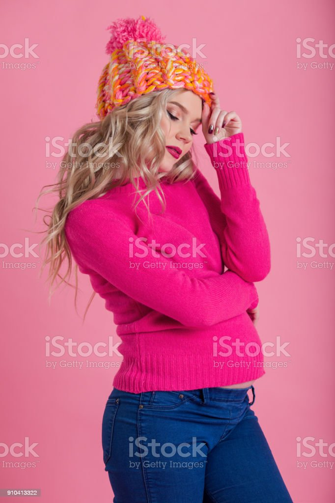 Beautiful happy pregnant woman is wearing warm winter clothes hat and sweater isolated on pink background stock photo