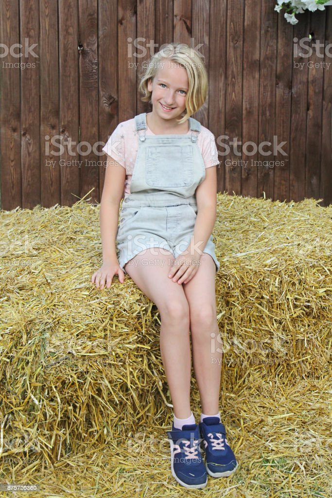 Beautiful happy preteen girl dressed in short bib overalls sitting on a hay in the village. Country style. stock photo