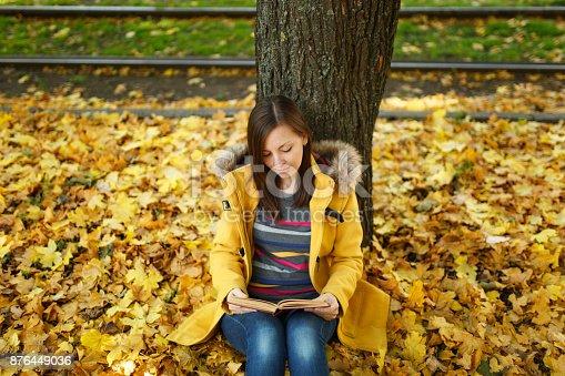 Fotografía de Una Feliz Sonriente Pelo Castaño Mujer Bella Capa Amarilla Y  Los Pantalones Vaqueros Sentados Debajo Del árbol De Arce Con Un Libro Rojo  En El ... 3aab0e8a30e0