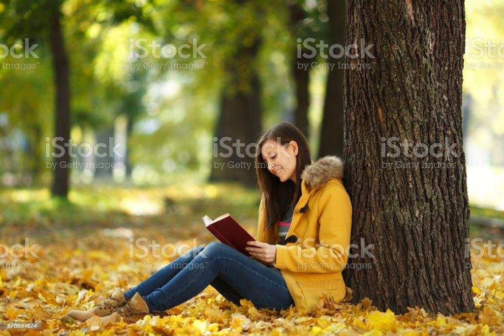 Una feliz sonriente pelo castaño mujer bella capa amarilla y los pantalones  vaqueros sentados debajo del 1d03b0ccf675