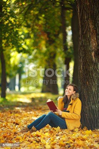 istock Una feliz sonriente pelo castaño mujer bella capa amarilla y los pantalones  vaqueros sentados debajo 80df4444831b