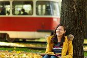 ... Una feliz sonriente pelo castaño mujer bella capa amarilla y los pantalones  vaqueros sentados debajo del ... db13945f225e