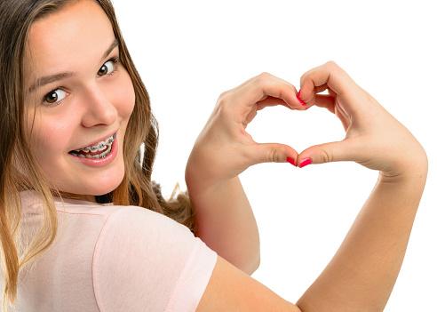 Beautiful happy teenage girl shows gesture heart. stock photo