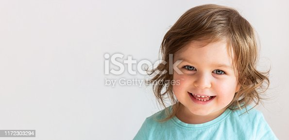 Beautiful happy toddler child girl smiling, portrait neutral background, space for text