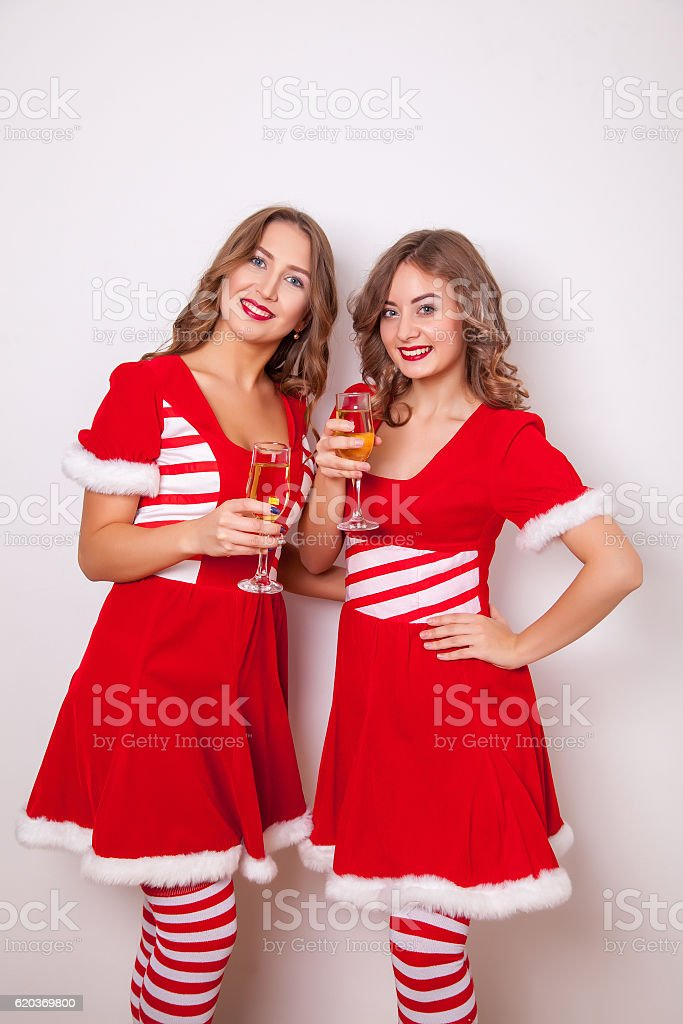 Beautiful Happy two girls in Santa Claus clothes with a zbiór zdjęć royalty-free