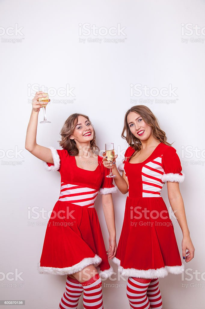 Beautiful Happy two girls in Santa Claus clothes with a foto de stock royalty-free